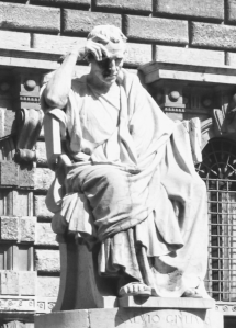 A classical Roman sculpture of a man in contemplative seated pose.